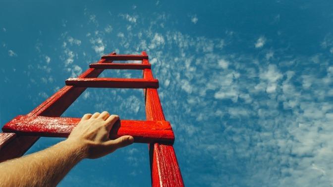 Eine rote Leiter ragt aufgestellt in die Höhe. Eine Hand umgreift eine der unteren Sprossen.