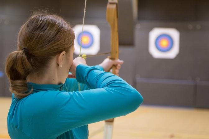 Eine Frau schießt mit Pfeil und Bogen auf ein Ziel