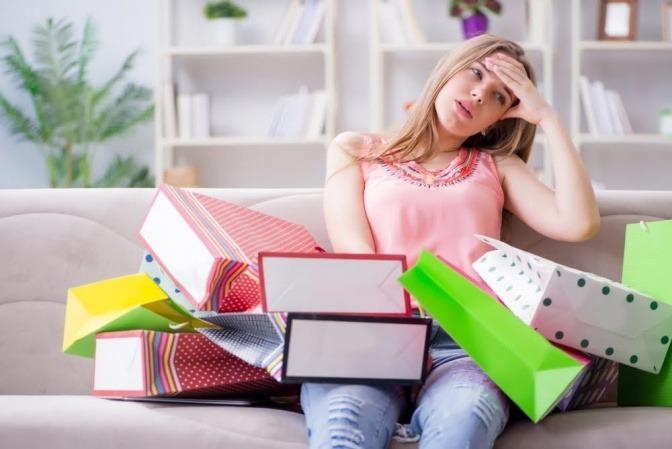Eine Frau sitzt auf einem Sofa, auf ihrem Schoß und um sie herum liegen diverse Einkaufstüten. Sie wirkt resigniert und antriebslos.