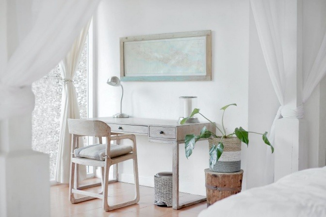 Neben dem Bett in einem Schlafzimmer steht eine grüne Zimmerpflanze auf einem Tisch