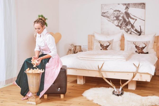 Eine Frau sitzt in einem aufgeräumten Schlafzimmer aus Zirbenholz
