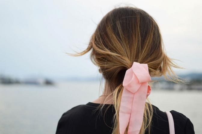 Eine Frau trägt einen Zopf mit einem rosafarbenen Haarband