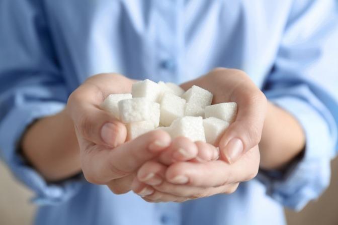 Eine Frau hält Zuckerwürfel in ihren Händen