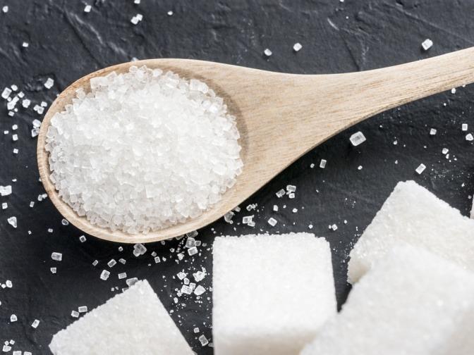 Zuckerwürfel neben einem Löffel mit Zucker