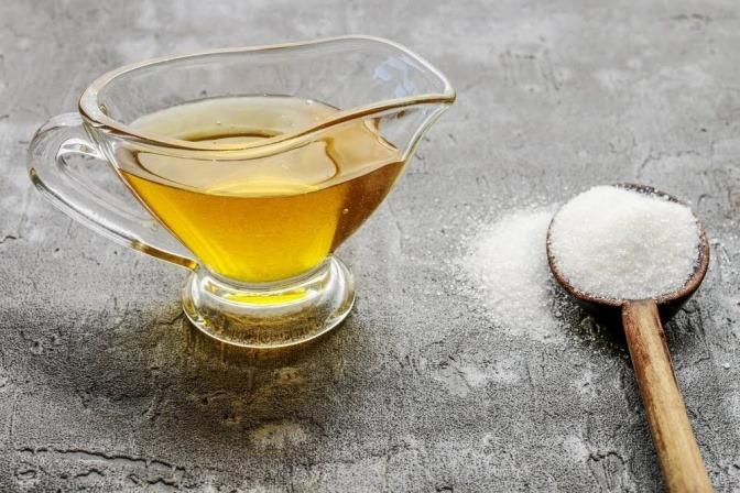 Eine kleine Karaffe mit Ahornsirup, daneben liegt ein Esslöffel mit Kristallzucker.