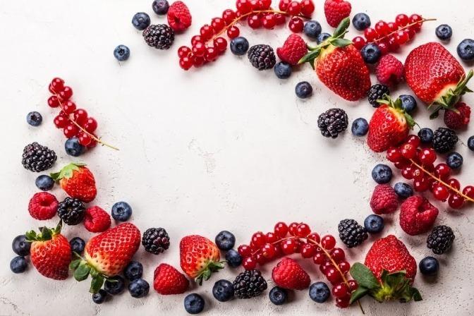 Verschiedene Früchte sind in einem Kreis auf einer weißen Unterlage angeordnet.
