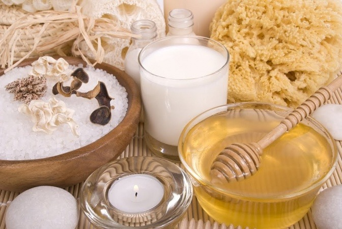 Eine kleine Glaskaraffe mit Honig, ein Honiglöffel und ein kleiner Haufen Mehl liegen auf einem Holzbrett.
