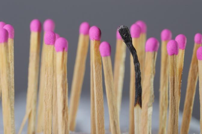 viele Zündhölzer stehen nebeneinander, eines ist abgebrannt
