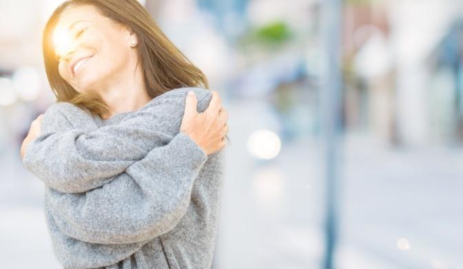 Eine Frau lacht und fühlt sich wohl bei schönem Wetter
