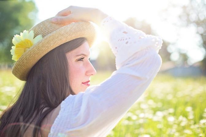 Eine Frau steht selbstliebend in der Wiese