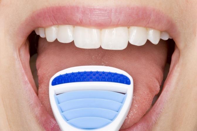 Die Zunge wird mit einem Schaber gereinigt
