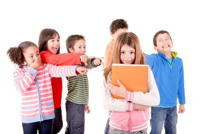 Eine Gruppe von Kindern lästert über ein anderes Kind.