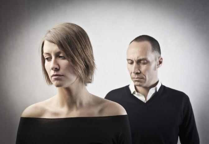 Ein Mann und eine Frau, beide mittleren Alters, sitzen hintereinander. Beide haben einen ernsten Gesichtsausdruck, die Frau sitzt mit dem Rücken zum Mann. Das Foto ist mit einem düster wirkenden Graufilter belegt.