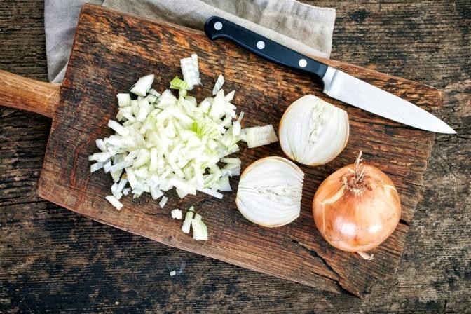 Gehackte Zwiebeln auf einem Holzbrett.