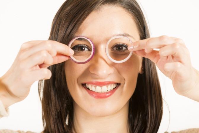 Frau hält sich Zwiebelringe vor das Gesicht gegen unreine Haut