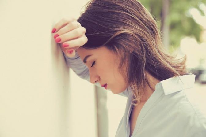 Eine Frau lehnt mit ihrem Kopf gegen eine Wand, vermutlich weil sie gestresst und gleichzeitig vom Mittagstief betroffen ist.