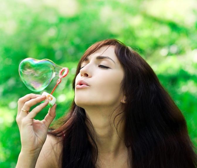 Eine junge Frau pustet Seifenblasen in der Form von Herzen durch die Luft.