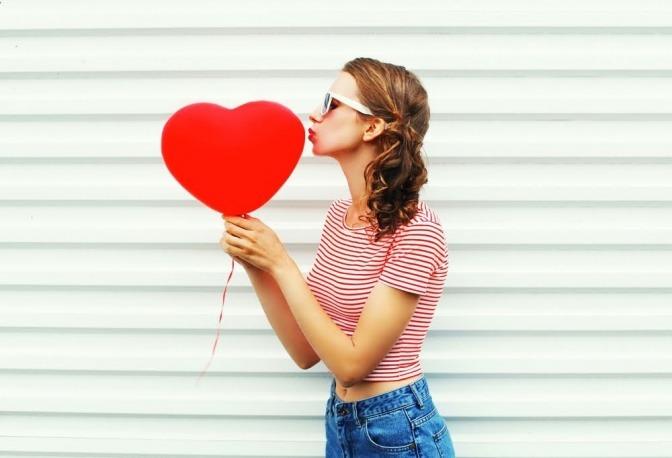 Eine Frau küsst einen roten Luftballon, der wie ein Herz geformt ist.