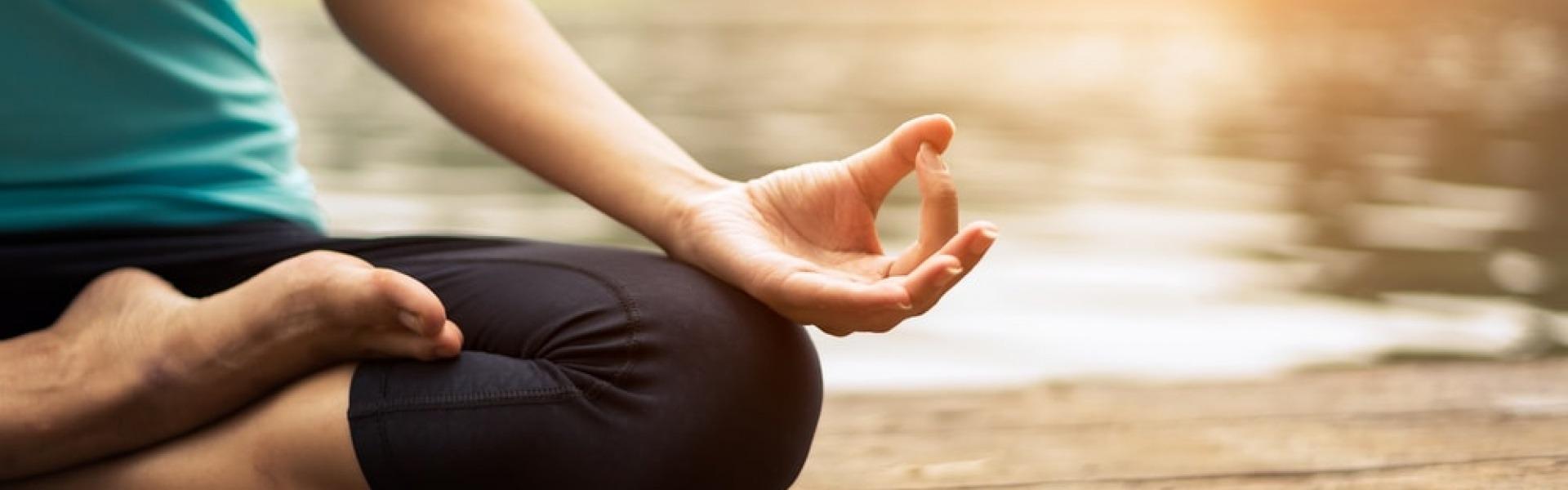 Eine entspannte Frau auf einem Steg meditiert