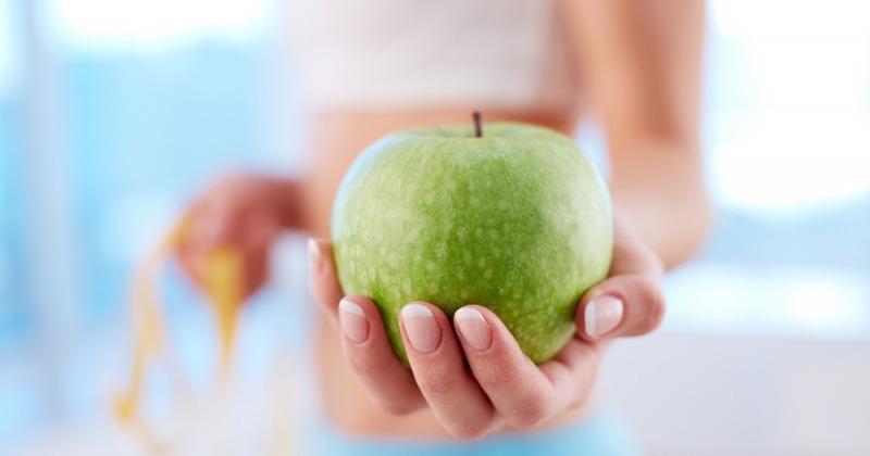 Eine Frau, die abnehmen möchte, hält einen Apfel