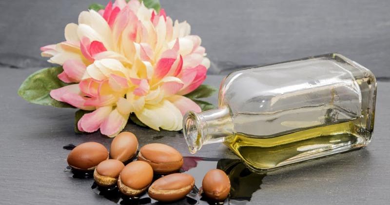 Aus einer Flasche fließt Arganöl, daneben liegen Früchte