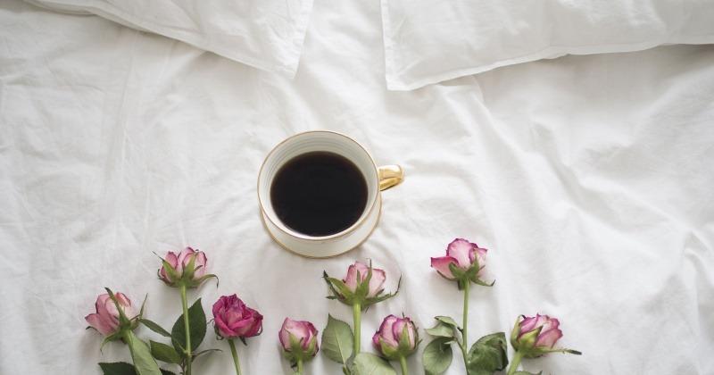 Eine Tasse mit Kaffee steht auf einem Bett mit Blumen darunter