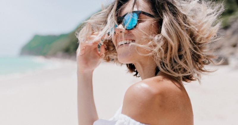 Eine Frau mit kurzen Haaren und Sonnenbrille