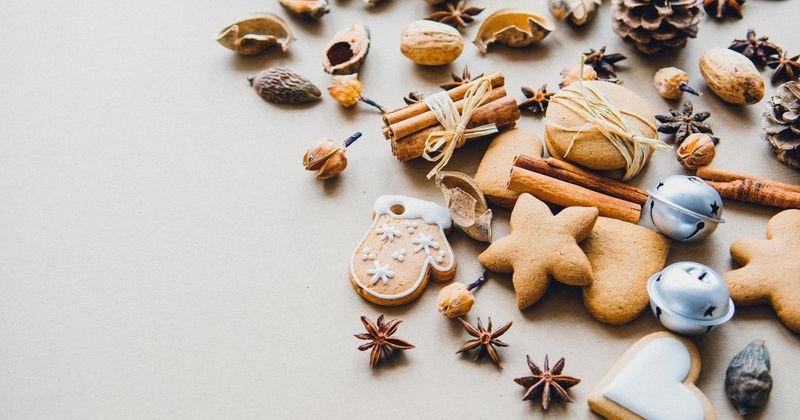 Verschiedene Kekse liegen neben winterlichen Gewürzen