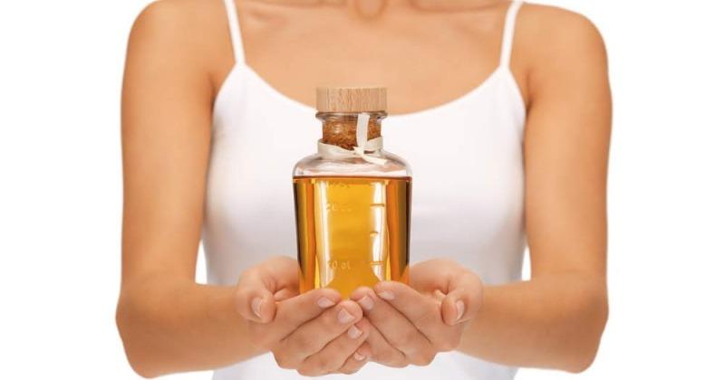 Eine Frau hält Öle als Medizin in einer Flasche