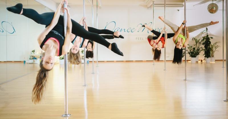 Frauen hängen kopfüber beim Poledance an der Stange