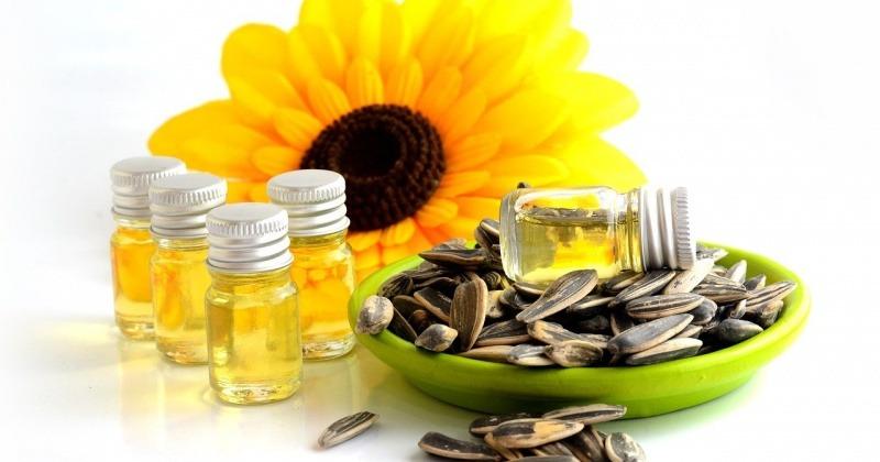 Sonnenblumenöl neben einer Sonnenblume und Sonnenblumenkernen