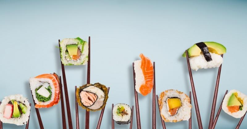 Verschiedene Sushi mit Reis werden mit Stäbchen gehalten