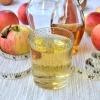 Apfelessig-Drink mit Essigflasche und frischen Äpfeln.