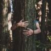 Eine Frau umarmt einen Baum