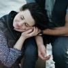 Eine Frau kniet auf dem Boden und legt Ihren Kopf in die Hände ihres Partners.
