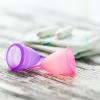 Binden, Tampons und Menstruationstassen liegen auf grauem Hintergrund