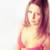 Eine Frau im BH sieht zufrieden aus und braucht keine Brustvergrößerung