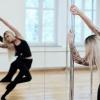 Eine blonde sportliche Frau tanzt vor einer Spiegelwand an einer Stange