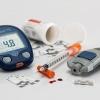 Ein Blutzuckermessgerät für Diabetes liegt neben Spritze und Messstreifen