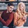 Ein junges Paar sitzt auf der Couch mit dem Handy in ihrer Handy