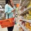 Eine Frau steht beim Einkauf im Supermarkt