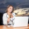 Eine erfolgreiche Frau mit Laptop und Kreditkarte sieht glücklich aus
