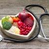 Essen zum Cholesterin senken liegt in einer Herzform, daneben ein Stetoskop