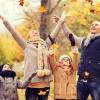 Familie im Herbst spielt mit Laub