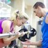 Ein Fitnesstrainer gibt einer Frau mit Hantel Anweisungen