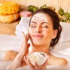 Eine Frau liegt in der Badewanne und trägt eine Gesichtsmaske auf