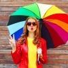Eine Frau hält einen bunten Regenschirm in ihrer Hand
