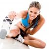 Eine braunhaarige Frau in Sportoutfit macht Dehnungsübungen. Sie blickt dabei direkt in die Kamera und lächelt.