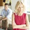 Frau steht mit verschränkten Armen vor sitzendem Mann mit Fernbedienung