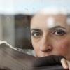 Eine Frau sieht traurig und nachdenklich aus dem Fenster
